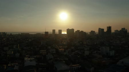 metropolitan area : Manila city with skyscrapers silhouettes at sunset, modern buildings and Makati business center, aerial drone. Travel vacation concept. Stock Footage