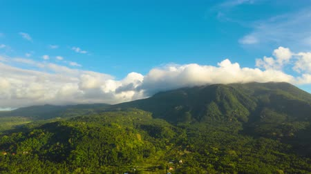 mindanao : Hyperlapse with running clouds over the mountains covered with rainforest. Camiguin, Philippines. Mountain landscape on tropical island with mountain peaks covered with forest. Slopes of mountains with evergreen vegetation. Stock Footage