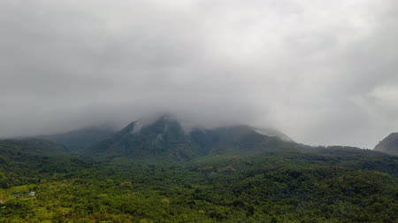 mindanao : Hyperlapse: Mountains covered rainforest, trees in cloudy weather, time lapse aerial view. Camiguin, Philippines. Mountain landscape on tropical island with mountain peaks covered with forest. Slopes of mountains with evergreen vegetation.