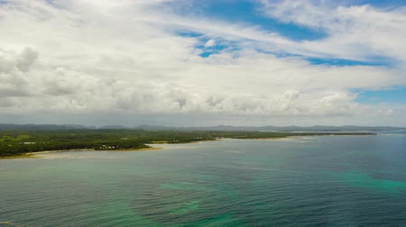 siargao island : Aerial timelapse: Blue sky with clouds over the coast of the island covered by rainforest top view. Summer and travel vacation concept Stock Footage