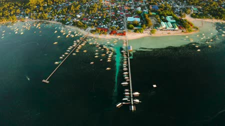 luna : City General Luna on the coast of Siargao with a pier, a port and tourist boats at sunrise, aerial view. Summer and travel vacation concept. Stock Footage