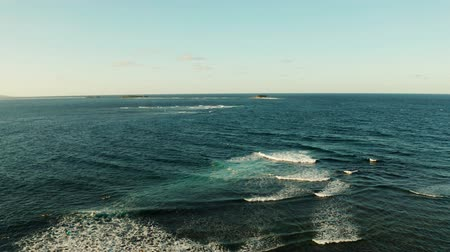 formação rochosa : Seascape with blue ocean and waves with rocky islands from above. Big waves crashing on the shore and coral. Summer and travel vacation concept Stock Footage