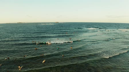 surfer paradise : Popular surf spot called cloud 9 on the island of Siargao and surfers on the waves at sunset, top view.