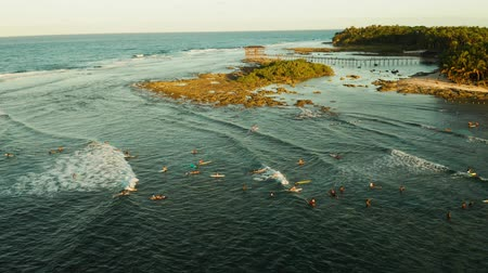 luna : Surf spot with surfers on the waves at sunset on the island of Siargao, cloud 9, Philippines. Aerial view.