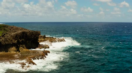 formação rochosa : Seascape: blue ocean and surf waves crashing on rocky coastline, top view. Siargao, Philippines. Summer and travel vacation concept Stock Footage