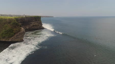 extreme : aerial view surfers on water surface ocean catch wave. People learning to surf bali, indonesia