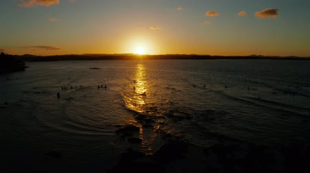 surfistas : Sunset above the sea with waves and surfers, aerial view. Reflected sun on a water surface. Siargao, Philippines. Sunset over ocean.