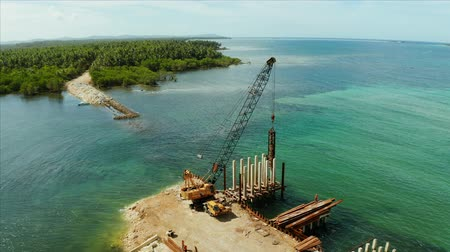 suspensão : Pile driver hammer in action. Construction bridge over the sea bay on the tropical island of Siargao.