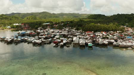 小屋 : Fishing village with boats and slums with wooden houses, aerial drone. Dapa, Siargao, Philippines.