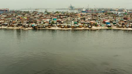 chata : Slums in Manila on the bank of a river polluted with garbage near the port, aerial view. Dostupné videozáznamy