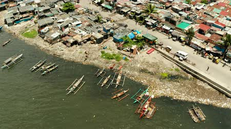 keet : Slums in Manila on the bank of a river polluted with garbage, aerial view.