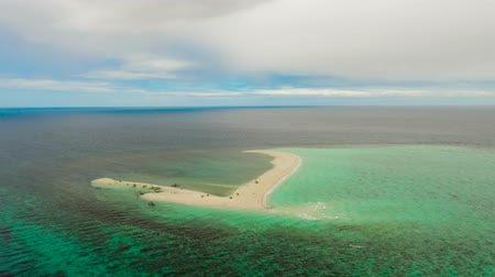island hopping : Hyperlapse: Sandy white island with beach and sandy bar in the turquoise atoll water, Time lapse aerial drone. Sandbar Atoll. Tropical island and coral reef. Summer and travel vacation concept, Camiguin, Philippines.