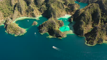 лодки : Aerial view tourist boats in lagoon. Kayangan Lake. lagoons, mountains covered with forests.coves with blue water among the rocks. Seascape, tropical landscape. Palawan, Philippines