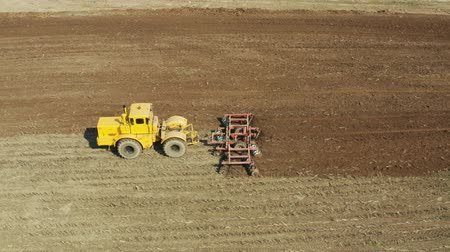 tırmık : aerial view farm tractor with disk plow preparing land for sowing. Tractor with harrows prepares the agricultural land for planting crop. Cultivation of farmland by disc harrows. Stok Video