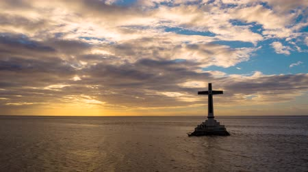 mindanao : Time lapse: Catholic cross in sunken cemetery in the sea at sunset, aerial view. Colorful bright clouds during sunset over the sea. Sunset at Sunken Cemetery Camiguin Island Philippines.