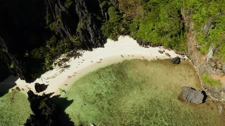 тропики : Aerial drone bay with beach and clear blue water surrounded by cliffs. El nido, Philippines, Palawan. tropical beach with palm trees. Seascape with tropical rocky islands, ocean blue water. Summer and travel vacation concept Стоковые видеозаписи