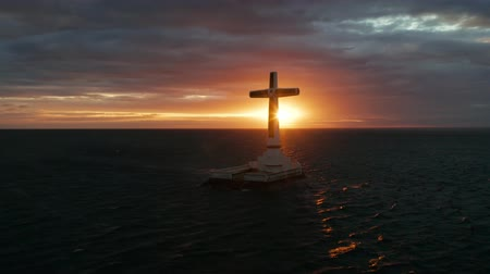 crucifix : Catholic cross in sunken cemetery in the sea at sunset, aerial drone. colorful sky during the sunset. Large crucafix marking the underwater sunken cemetary, Camiguin Island Philippines.
