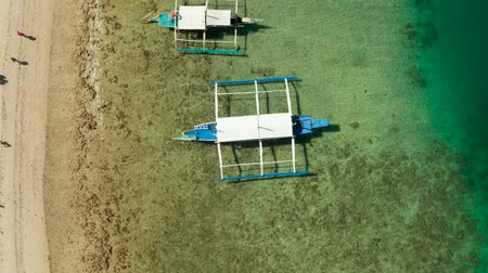 costa azzurra : Traditional Philippine boat on the surface of the azure water in the lagoon. Top view of boat from drone.