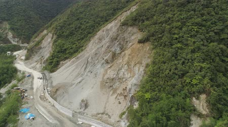 landslide : Construction protective barriers against rock falls and landslides in mountainous province. Aerial view heavy machinery on the construction of a mountain road. Cement block road protection from landslides. Philippines, Luzon, North Batad.