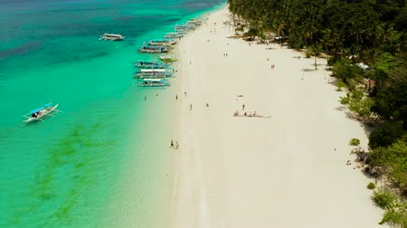 boracay : Coast with sandy beach with tourists and clear blue sea top view, Puka shell beach. Boracay, Philippines. Seascape with beach on tropical island. Summer and travel vacation concept.