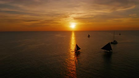 vela : Sailing boat silhouette during sunset, aerial view Boracay, Philippines. Reflected sun on a water surface. Sunset over ocean. Seascape, Summer and travel vacation concept Stock Footage