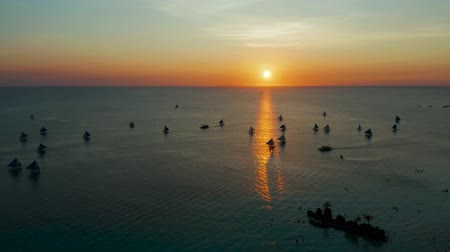 tükrözött : Sunset above the sea surface with sailing yachts, aerial view Boracay, Philippines. Reflected sun on a water surface. Sunset over ocean. Seascape, Summer and travel vacation concept Stock mozgókép