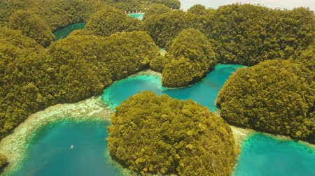 grande : aerial footage lot islands in lagoon with turquoise water Bucas Grande Island Sohoton Cove. islands covered with green tropical forest surrounded by beautiful bays and lagoons tropical seascape blue sea, azure lagoon. Flying over the azure surface ocean.