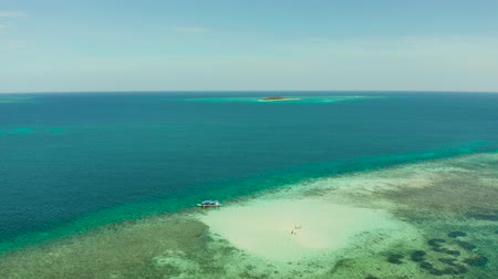 balabac : Sandy beach with tourists on a coral atoll in turquoise water, from above. Summer and travel vacation concept. Balabac, Palawan, Philippines.