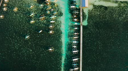 luna : Long pier with moored boats in the morning, aerial view. General Luna, Siargao island.