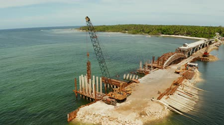 ponte sospeso : Pile hammer working on construction site. Bridge under construction over the sea bay connecting the two parts of Siargao island. Filmati Stock
