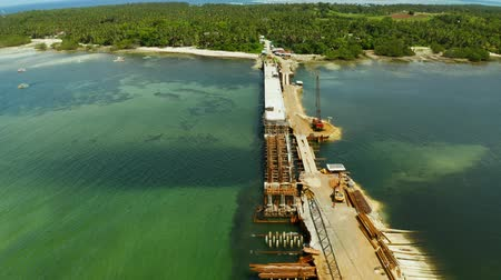 asma : Heavy construction equipment and workers in the construction of a bridge across the strait. Siargao, Philippines