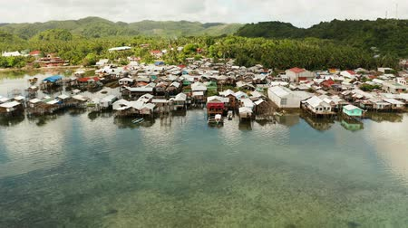 slum house : Old wooden house standing on the sea in the fishing village, aerial view. Dapa, Siargao, Philippines. Stock Footage