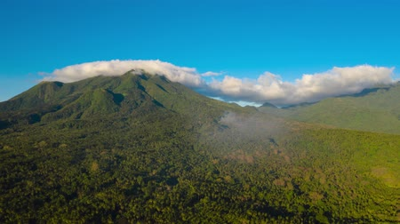 mindanao : Hyperlapse: Clouds in the blue sky over the tops of mountains covered in rainforest, time lapse.