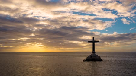 mindanao : Timelapse: Catholic cross in sunken cemetery in the sea at sunset, aerial view. Colorful bright clouds during sunset over the sea. Sunset at Sunken Cemetery Camiguin Island Philippines.