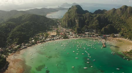 palawan : Aerial view of town of El Nido in the bay with the blue lagoon and tourist boats. Famous tourist place on the island of Palawan. Seascape with blue bay and boats view from above. Summer and travel vacation concept