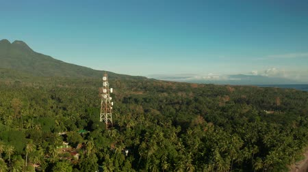 továbbít : Telecommunication tower, communication antenna against mountains and rainforest, aerial view. Repeaters on a metal tower. Camiguin, Philippines