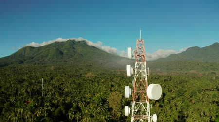 reflektör : Telecommunication tower, communication antenna against mountains and rainforest, aerial view. Repeaters on a metal tower. Camiguin, Philippines
