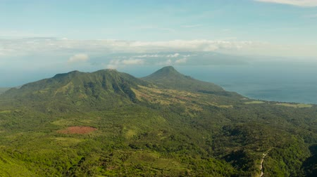 mindanao : Mountains covered rainforest, trees and against blue sea with blue sky with clouds, aerial view. Camiguin, Philippines. tropical landscape. Mountain landscape on tropical island with mountain peaks covered with forest. Slopes of mountains with evergreen v Stock Footage