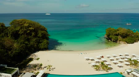 boracay : Tropical sandy beach and bay with azure water at the hotel with swimming pool and sun beds Boracay, Philippines. Seascape with beach on tropical island. Summer and travel vacation concept.