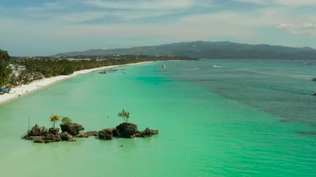 boracay : White sand beach and Willys rock with tourists and hotels and sailing boat on Boracay Island. Aerial drone: Tropical white beach with sailing boat. Summer and travel vacation concept.