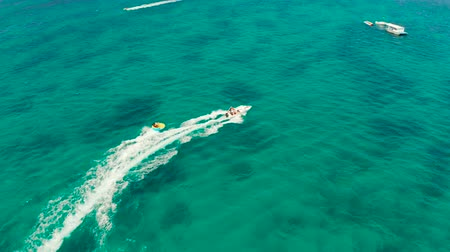 nafukovací : Happy people ride the inflatable watercraft raft. Sea attraction, aerial view. Water sports and recreation on a tropical island. Summer and travel vacation concept Dostupné videozáznamy