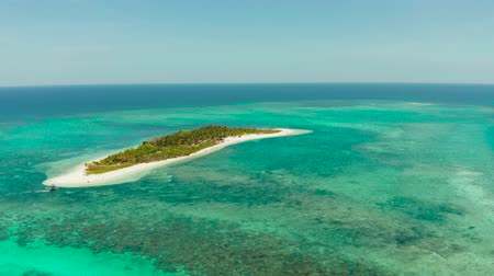 island hopping : Tropical island on an atoll with beautiful sandy beach by coral reef from above. Canimeran Island and coral reef. Summer and travel vacation concept. Stock Footage