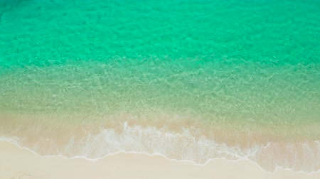 tyrkysový : Sandy beach with and azure water of the lagoon,copy space for text, top view. Sea water surface in lagoon. Transparent turquoise ocean water surface. Background texture