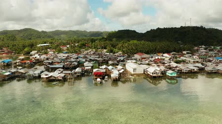 slum house : Fishing village with boats and slums with wooden houses, aerial drone. Dapa, Siargao, Philippines.