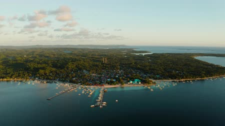 luna : Coastal town General Luna on the island of Siargao, with a pier, port and boats at sunrise top view. Surfing place. Summer and travel vacation concept.