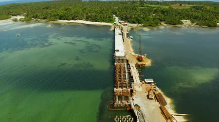 süspansiyon : Construction of a new bridge over the sea bay on the tropical island of Siargao. Stok Video