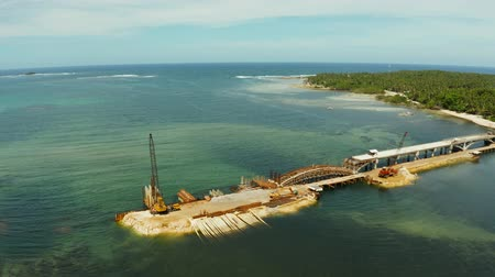 asma : The bridge under construction across the bay and construction equipment with workers on the bridge. Siargao, Philippines.