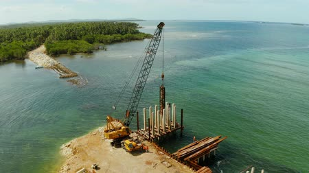 suspensão : Construction of a new bridge over the sea bay on the tropical island of Siargao. Stock Footage
