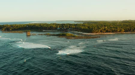 siargao island : Popular surf spot called cloud 9 on the island of Siargao and surfers on the waves at sunset, top view.