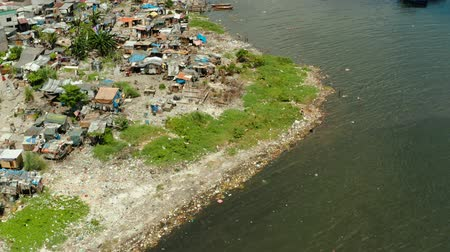 slum house : Slums with shacks of local residents and the river bank littered with garbage from above. Manila, Philippines. Stock Footage
